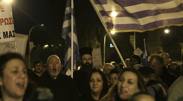 Protesters shout slogans and wave Greek flags during a protest against the handling of reunification talks (Petros Karadjias/AP)