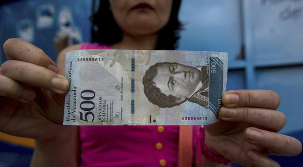 A bank customer shows a new bank note of 500 bolivars outside a bank in Caracas, Venezuela (AP)
