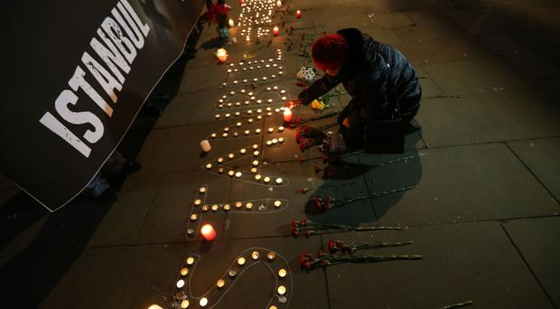People take part in a vigil after the attack on an Istanbul nightclub which left 39 people dead