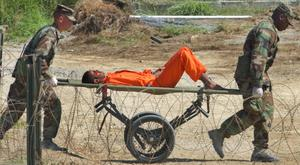 A detainee from Afghanistan is carried on a stretcher before being interrogated by military officials at the detention facility Camp X-Ray in Guantanamo Bay (AP)
