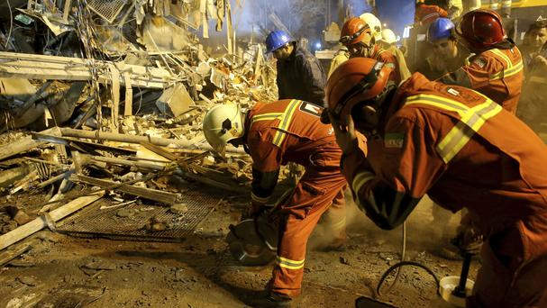 Iranian firefighters start to dig a tunnel to make a corridor under the 17-storey Plasco building which collapsed after being engulfed by a fire in central Tehran (AP/Ebrahim Noroozi)