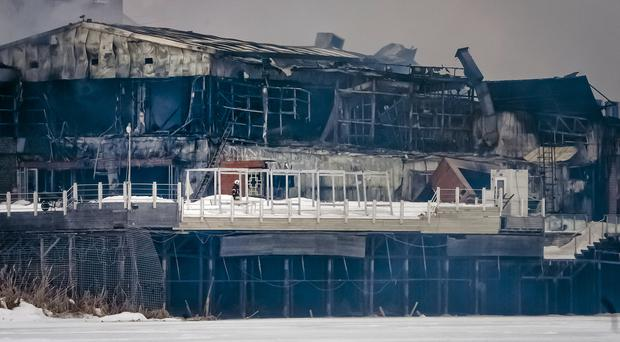 A firefighter stands on the terrace of the nightclub wrecked by fire
