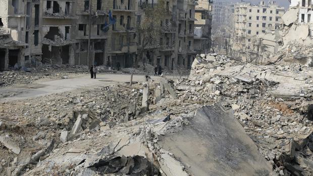 Residents walk near mounds of rubble in Aleppo, Syria (AP/Hassan Ammar)