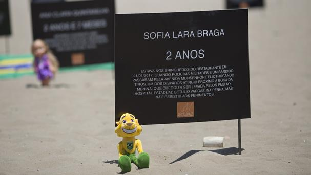 Signs that bear the names of children killed by stray bullets line Copacabana beach in Rio, Brazil (AP/Silvia Izquierdo)