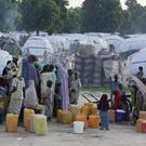 People displaced by Islamist extremists fetch water at the Muna camp in Maiduguri, Nigeria (AP)
