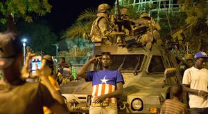 Gambians pose in front of military vehicles as Ecowas troops from Senegal secure the area near the State House in the capital Banjul (AP)