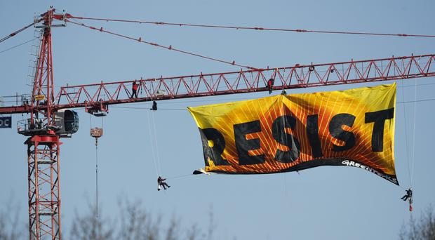 Protesters unfurl a banner that reads Resist at the construction site of the former Washington Post building in Washington (Pablo Martinez Monsivais/AP)
