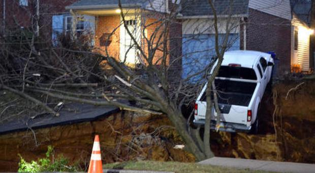 A pick-up truck dangles over the edge of a sinkhole in the Philadelphia area (Emily Casher Loomis via AP)