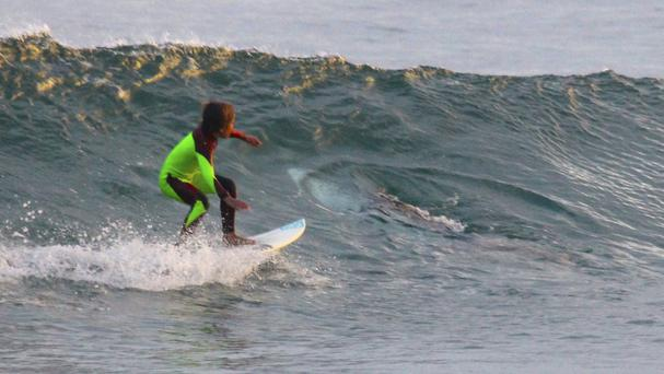 Eden Hasson, 10, surfs near what is believed to be a great white shark (Chris Hasson/AP)
