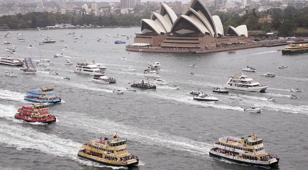 Competitors in the annual ferry boat race are supported by a spectator flotilla as they cruise past Sydney Opera House as part of Australia Day celebrations (AP)