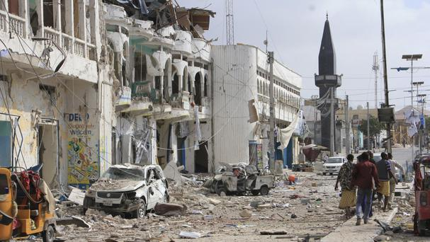 Somalis walk near the destroyed hotel and cars in Mogadishu (AP)