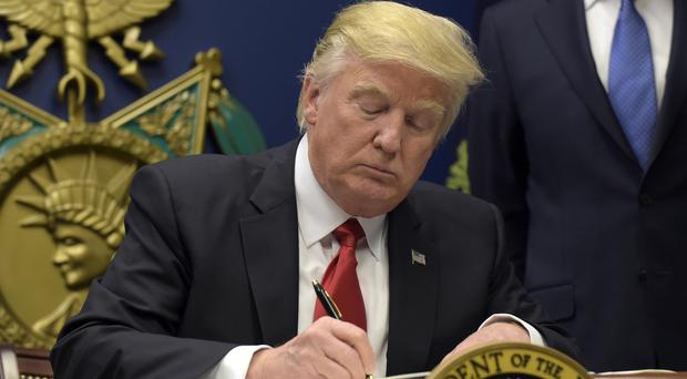 Donald Trump signs the executive extreme vetting order at the Pentagon (AP)