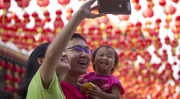 A Malaysian ethnic Chinese family take a selfie on the first day of Chinese Lunar New Year at a temple in Kuala Lumpur, Malaysia (AP)