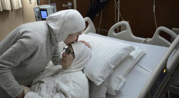 Nour Ulayyet comforts her sick mother Isaaf Jamal Eddin in hospital after her sister, a Syrian living in Saudi Arabia with a valid visa, was sent back from Chicago's O'Hare International Airport (AP Photo/Paul Beaty)