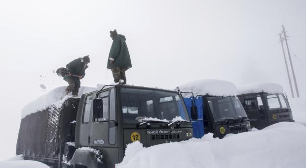 Indian Army soldiers clear snow from their stranded vehicles near a base camp in Gulmarg, about 34 miles north-west of Srinagar (AP)