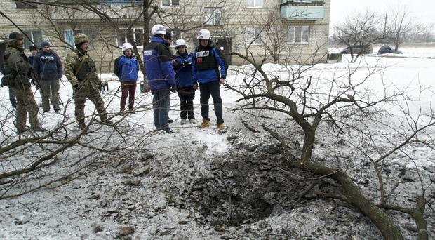 OSCE monitors examine a crater after shelling in Avdiivka, eastern Ukraine (AP/Inna Varenytsia)