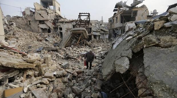 A resident walks amid the rubble in Aleppo, Syria (AP/Hassan Ammar)