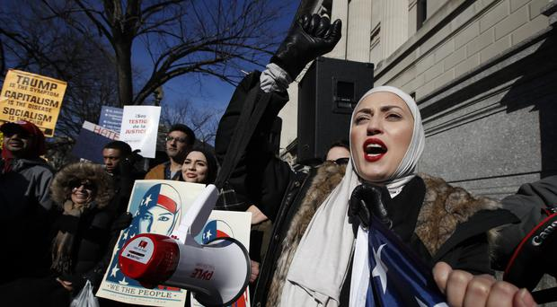 A demonstrator chants during a rally protesting over the immigration policies of US president Donald Trump, near the White House in Washington (AP)
