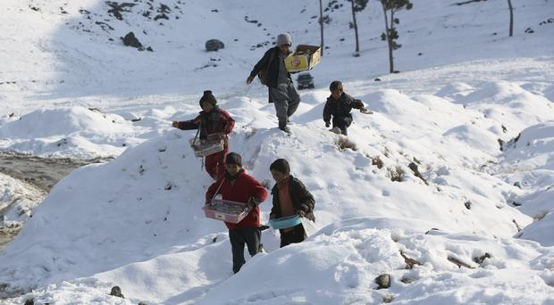 Child street vendors carry their wares as they walk through snow on the outskirts of Kabul (Rahmat Gul/AP)