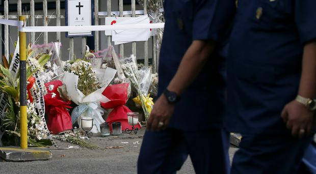 Philippine National Police officers walk past the makeshift memorial where a South Korean businessman was killed allegedly by active police officers (Bullit Marquez/AP)