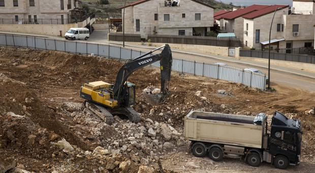 Israel is moving ahead with a contentious law that would legalise dozens of settlement outposts in the West Bank (AP)