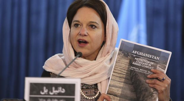 Unama's Danielle Bell holds a copy of the UN 2016 Annual Report on the Protection of Civilians in Armed Conflict in Afghanistan (AP)