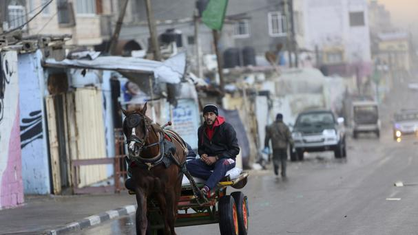A man rides a horse cart along the beach as rainy and heavy winds prevail on the Mediterranean Sea, at beach road of Shati refugee camp in Gaza City (AP)