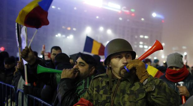 Protesters blow horns during a protest in Bucharest, Romania (Darko Bandic/AP)