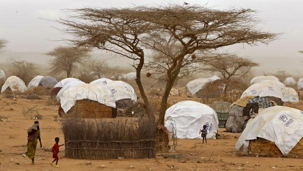 Refugees walk among huts at the refugee camp in Dadaab (AP)