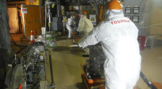 Workers prepare to operate a remote-controlled 'cleaning' robot at Unit 2 of Fukushima Dai-ichi nuclear power plant (Tepco via AP)