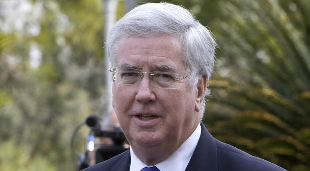 Sir Michael Fallon arrives at the presidential palace for a meeting with Cypriot President Nicos Anastasiades in the capital Nicosia (Petros Karadjias/AP)