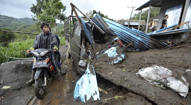 A motorist rides past the wreckage of a truck partially buried under the mud following a landslide in Songan village on Bali island (AP)