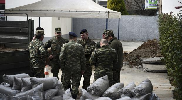 Military officers in Thessaloniki, where an unexploded Second World War bomb has been found (Giannis Papanikos/AP)