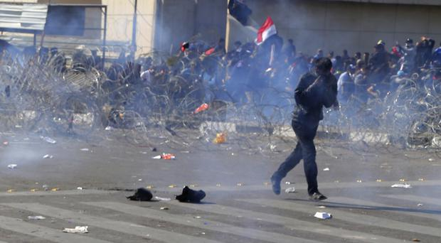 Protesters run from tear gas fired by security forces during protests for followers of Iraq's influential Shiite cleric Muqtada al Sadr in Tahrir square, Baghdad (AP/Karim Kadim)