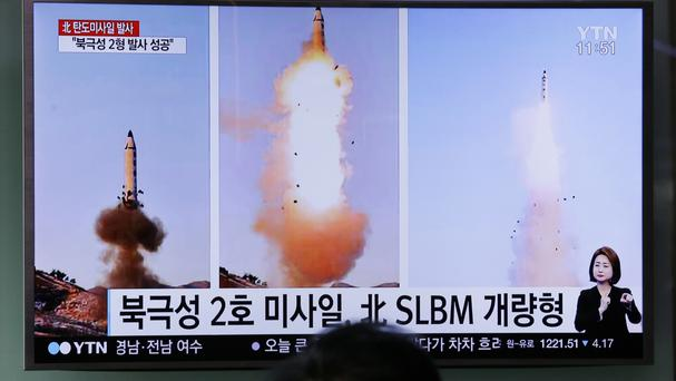 A South Korean TV news programme shows photos published in North Korea's Rodong Sinmun newspaper of Pyongyang's Pukguksong-2 missile launch (AP)