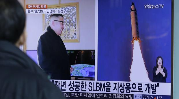 A man in Seoul watches a TV news programme showing photos published in North Korea's Rodong Sinmun newspaper of North Korea's latest missile launch (AP/Ahn Young-joon)