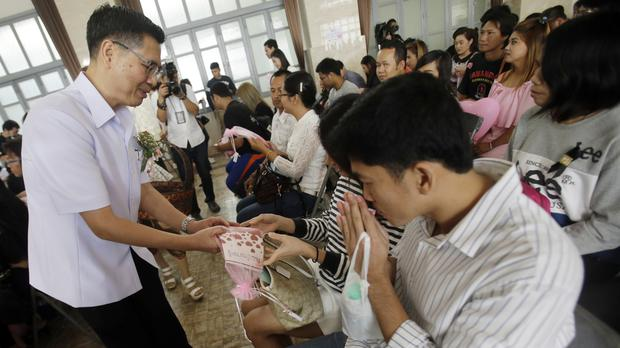 Pills containing folic acid and iron are handed to couples waiting to sign their marriage certificates in Bangkok (AP Photo/Sakchai Lalit)