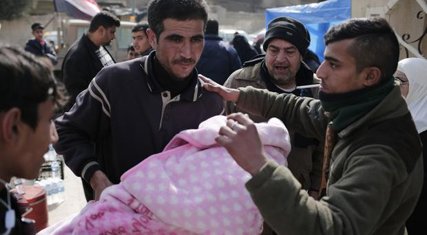 A man carries a wounded child to a hospital in the Zahra neighbourhood of Mosul (AP)