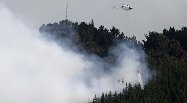 A helicopter dumps water on a wild fire in the Port Hills near Christchurch (AP Photo/Mark Baker)