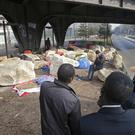 Migrants gather under a railway bridge in Paris (Michel Euler/AP)