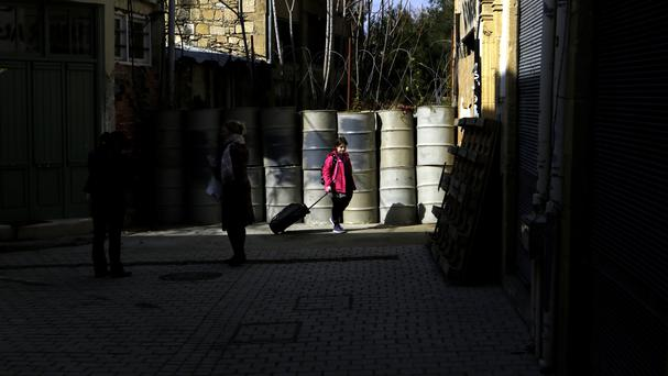 A young woman pulls her suitcase as she walks by the barrels that block a road from the Greek Cypriot-controlled area to the Turkish Cypriot north in Nicosia (Petros Karadjias/AP)