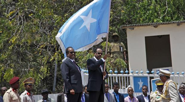 Somalia's President Mohamed Abdullahi Farmajo holds a Somali flag during a handover ceremony at the presidential palace in Mogadishu (Farah Abdi Warsameh/AP)
