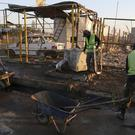 Workers clean up after a suicide car bomb attack in a neighbourhood of Baghdad (Karim Kadim/AP)