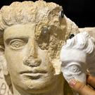 Restorer Daria Montemagni shows a computer-rendered, 3D print-generated replica of a missing part of a limestone female bust (Domenico Stinellis/AP)