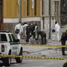Police and investigators inspect the site where a homemade bomb exploded near the Santamaria bull ring in Bogota (AP)