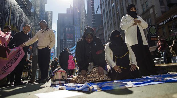 Women pray during a rally in support of Muslim Americans and protesting against President Donald Trump's immigration policies in Times Square, New York (AP/Andres Kudacki)