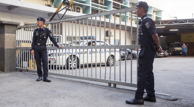Malaysian police officers guard the gate of the forensic department at Kuala Lumpur Hospital (AP Photo/Alexandra Radu)