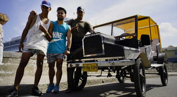 Dany Gomez, centre, and friends show off his pedal-powered Model-T Ford replica in Havana (AP)