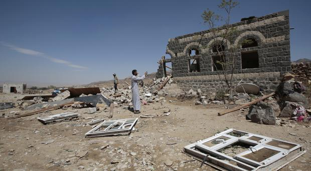 A man takes a photograph of a house destroyed by a Saudi-led air strike in the outskirts of Sanaa, Yemen (AP/Hani Mohammed)