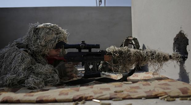 A sniper with the Iraqi federal police aims at an Islamic State position from the rooftop of a house in the town of Abu Saif, as part of the battle for Mosul.